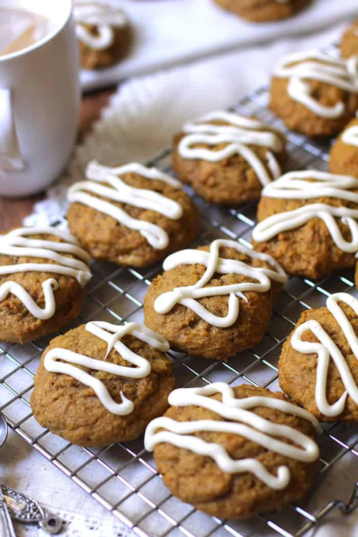 A side angle of iced pumpkin cookies on a cooling rack with a cup of coffee in the background.