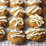 A side view of iced pumpkin cookies on a wire cooling rack, with a white napkin underneath.