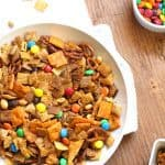 Overhead shot of a round white bowl full of Chex party mix, on a white napkin placed on a wooden background.