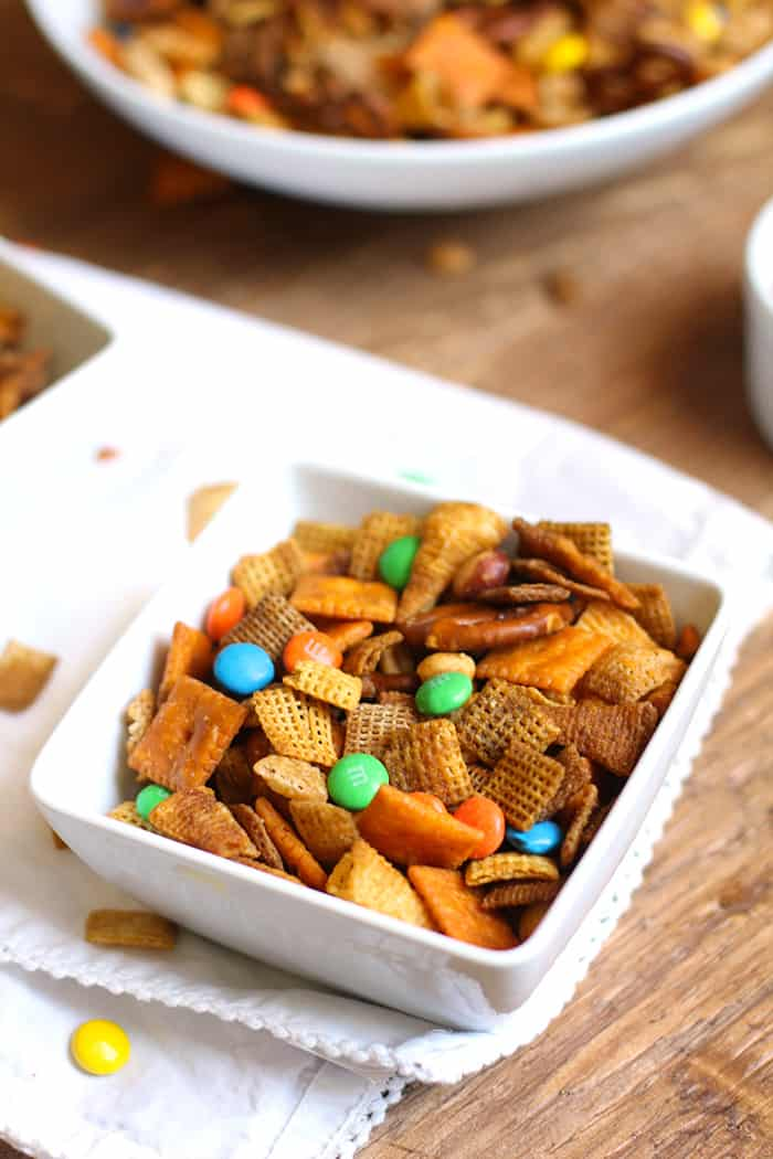 Overhead shot of a small square white dish full of Chex party mix, on a white napkin placed on a wooden background.