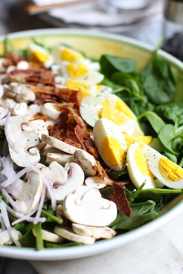 Side shot of a large yellow bowl with spinach salad, including onions, mushrooms, bacon, and eggs.