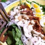 Side shot of a large yellow bowl with spinach salad and Honey Dijon dressing.