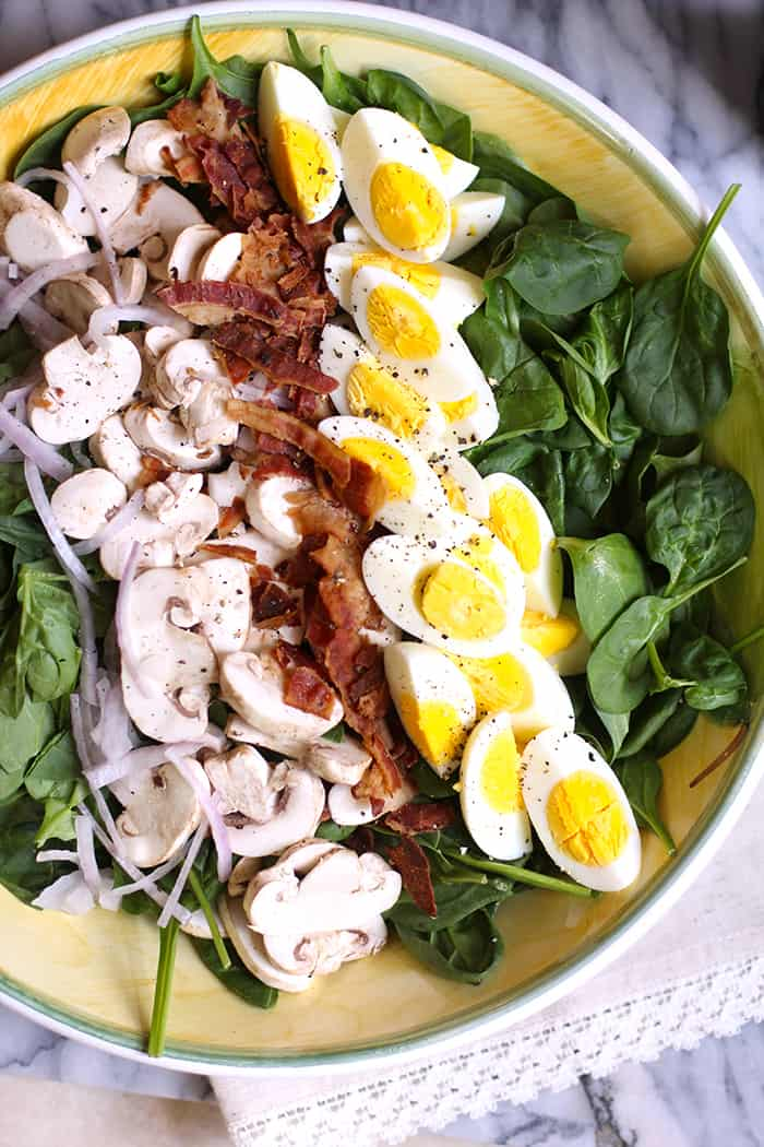 Overhead shot of a large yellow bowl filled with spinach salad, layered with red onion, sliced mushrooms, crumbled bacon, and hard-boiled eggs.