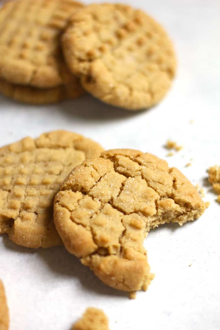 Side shot of peanut butter cookies on a white background, with a big bite out of one.