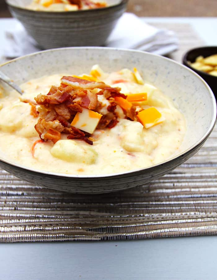 Side shot of a bowl of chunky loaded potato soup, with bacon on top.