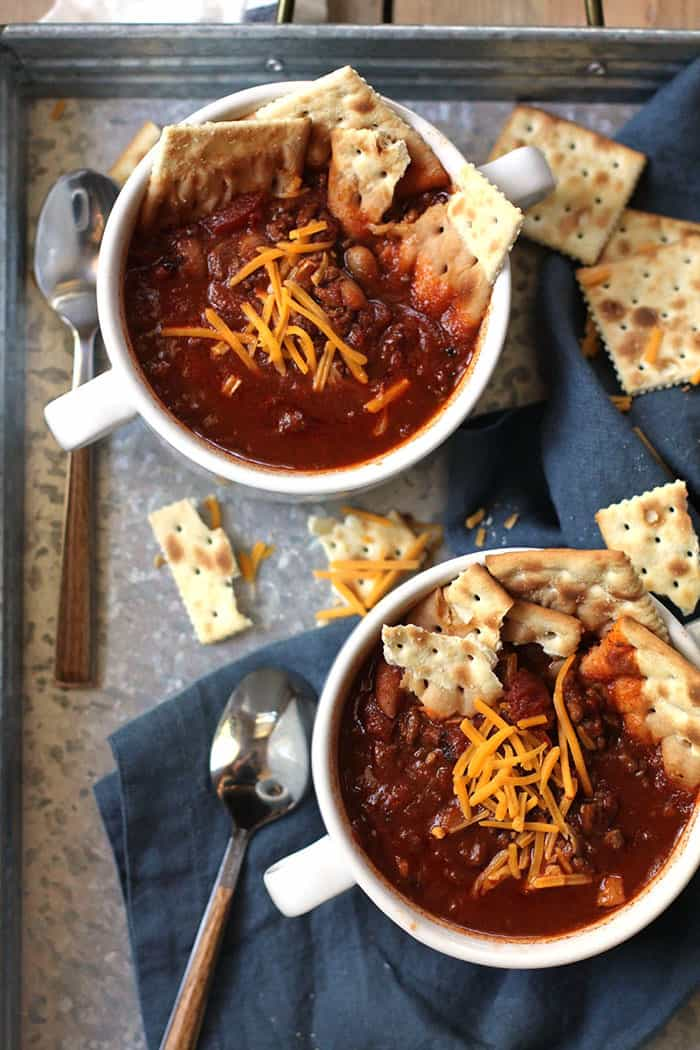 Overhead shot of two bowls of slow cooker chili, with crackers inside the bowls, on a gray tray with a blue napkin and spoons.