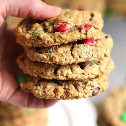Close up shot of my hand holding a stack of four monster cookies.