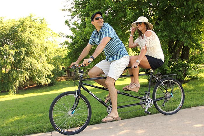 My husband and I on a tandem bike in a park, riding on a sidewalk and smiling.