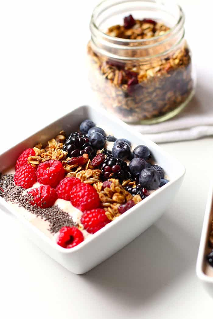 An Acai Smoothie Bowl, with a jar of granola in the background.