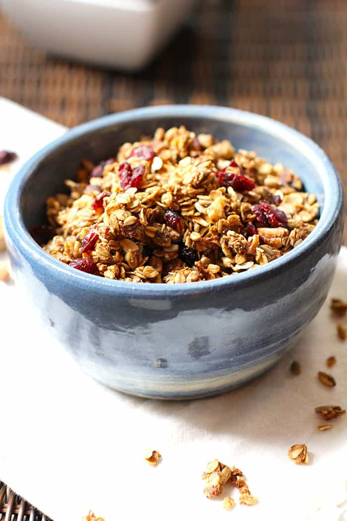 Side shot of a round blue bowl, filled with granola, on a wicker tray.