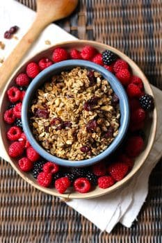 Overhead shot of a round blue bowl of granola, wet inside a tan shallow bowl, with raspberries and blackberries inside that bowl.