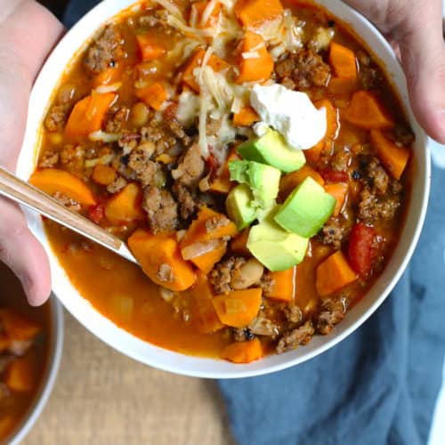 Two hands holding a white bowl of sweet potato turkey chili, over a wooden background with a blue napkin.