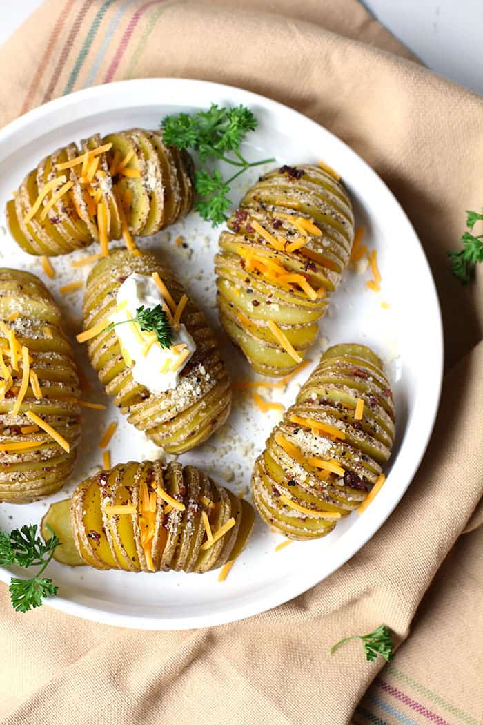 Baked Hasselback Potatoes are a unique twist on simple potatoes. Sliced thin with a rub of olive oil, butter, salt & pepper - topped with cheese and bacon.