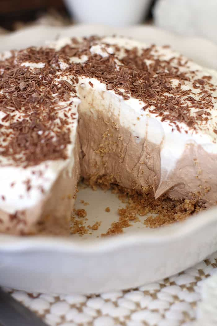 A side close-up shot of French silk pie in a white pie plate, with one piece missing, so you can see the layers.