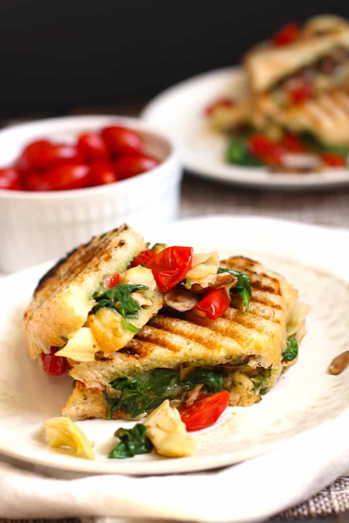 Side shot of a roasted vegetable pesto panini, on a white plate.