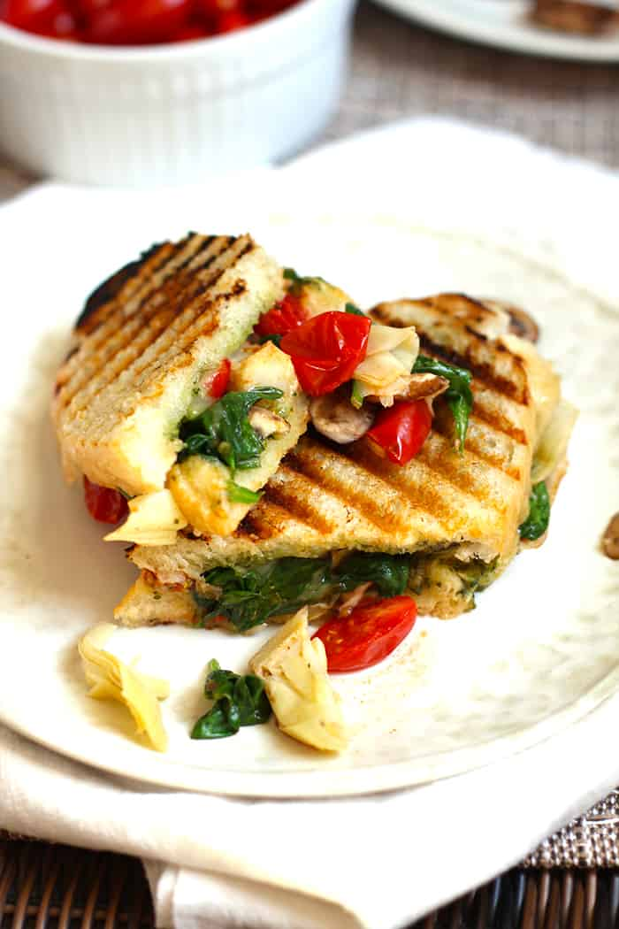 Overhead shot of a roasted vegetable pesto panini, on a white plate.