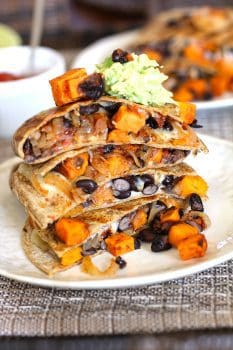 Sweet Potato and Black Bean Quesadillas -- a meatless quesadilla, full of sweet potatoes, black beans, onions, and a spicy kick - topped with guacamole and salsa! | suebeehomemaker.com