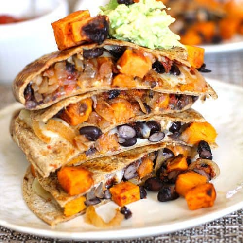 A tall stack of sweet potato and black bean quesadillas, on a white plate.