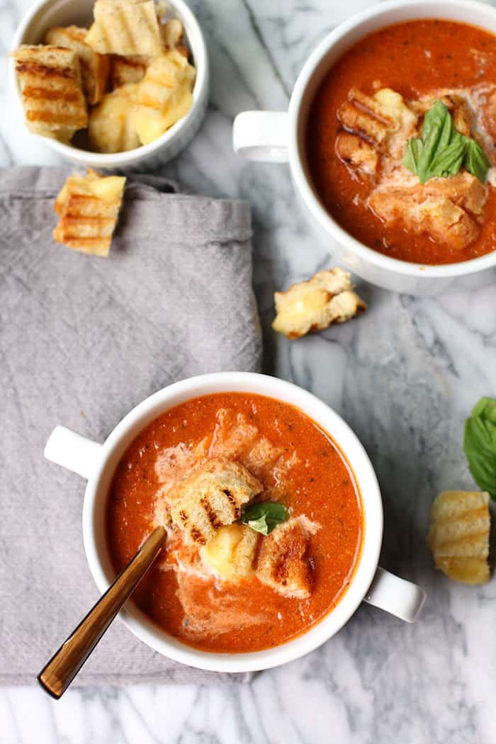 Classic tomato soup made with tomatoes, onion, dried basil, and half and half - topped with sourdough grilled cheese croutons and fresh basil! | suebeehomemaker.com