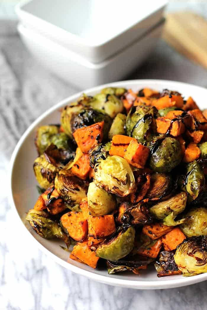A delicious side dish of roasted brussels sprouts and sweet potatoes, topped with a Balsamic drizzle!