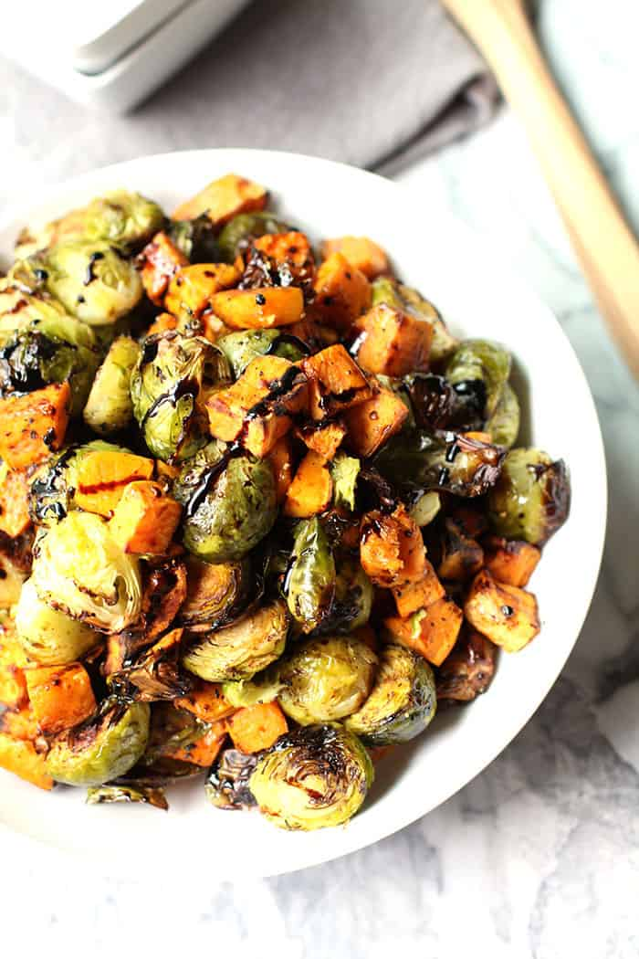 A delicious side dish of roasted brussels sprouts and sweet potatoes, topped with a Balsamic drizzle! | suebeehomemaker.com