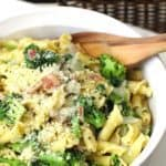 Closeup of a large white bowl of broccoli pasta with bacon.