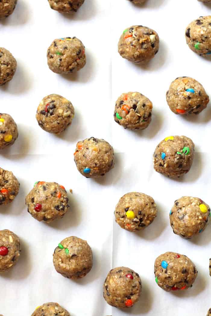 Overhead shot of cookie balls before the chocolate coating, showing m&ms and mini chocolate chips throughout, all on white parchment paper.