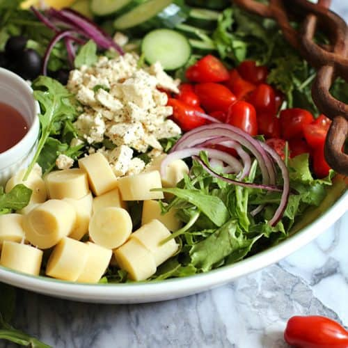 Overhead shot of a large bowl of Italian Hearts of Palm Salad, with ingredients in sections and two wooden spoons.