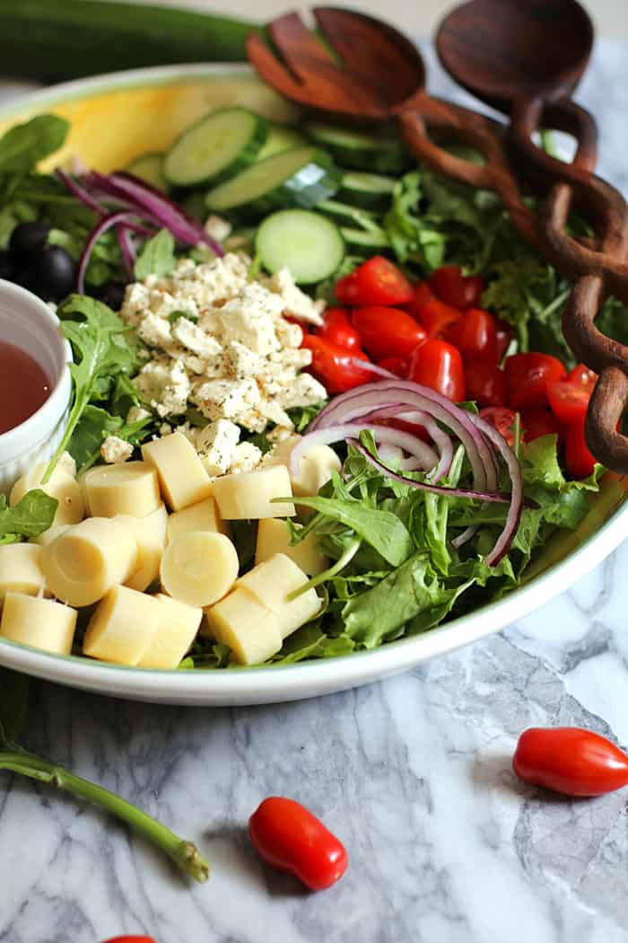 Italian Hearts of Palm Salad - fresh and vibrant and full of greens, cherry tomatoes, cucumber, red onion, black olives, hearts of palm, and a red wine vinaigrette! | suebeehomemaker.com