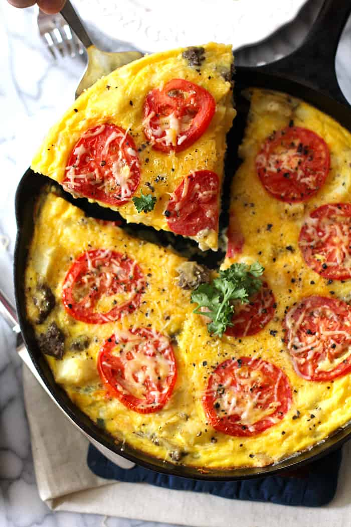 Overhead shot of a cast iron skillet of sausage potato breakfast frittata, with one piece being lifted out.