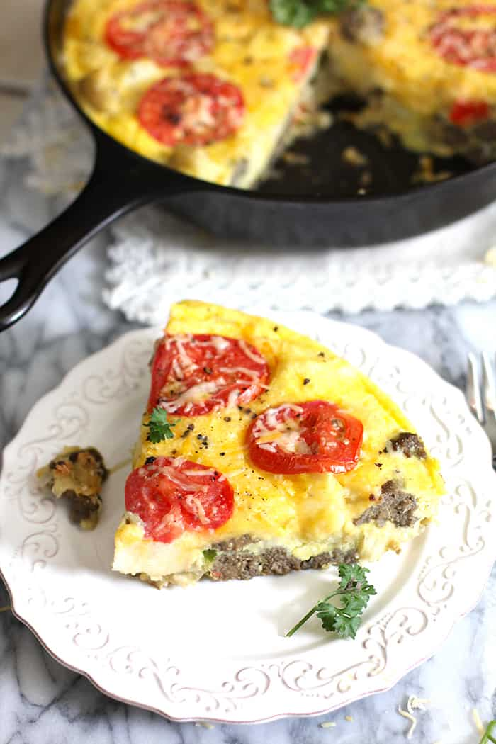 Side shot of a slice of breakfast frittata, with tomatoes on top.