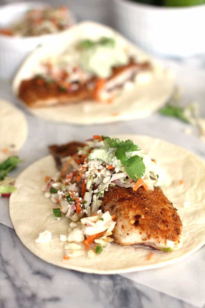 Easy Fish Tacos with Avocado Crema - super easy fish tacos, combining baked tilapia with a spice rub, a crunch veggie slaw, topped with an avocado crema! | suebeehomemaker.com