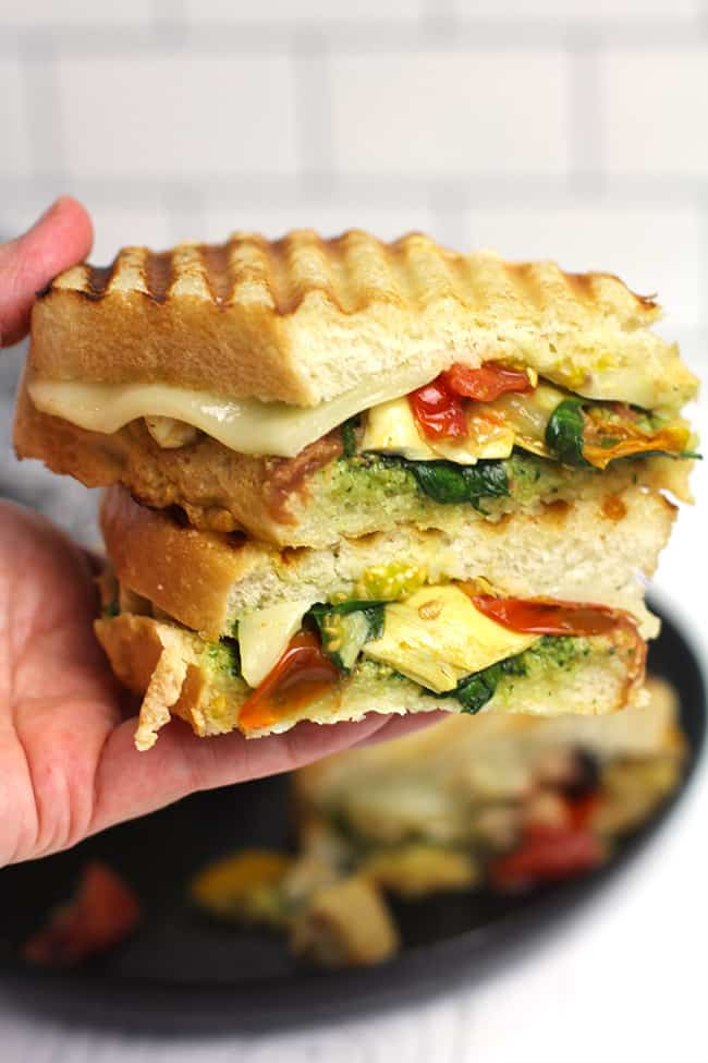 Side shot of my hand holding a double stack of roasted vegetable pesto panini, sliced in half.