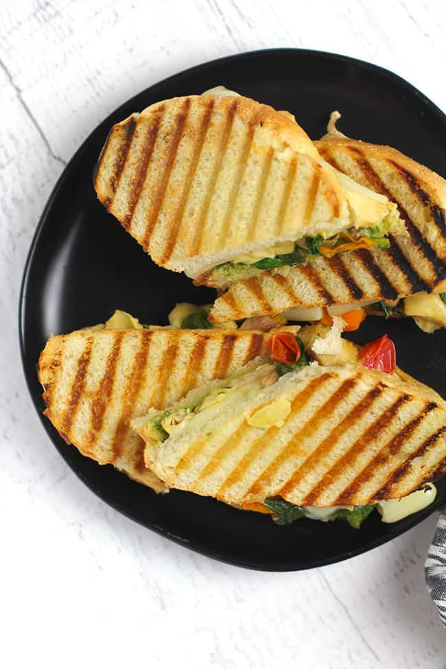 Overhead shot of a black plate of roasted vegetable pesto paninis, sliced in half.