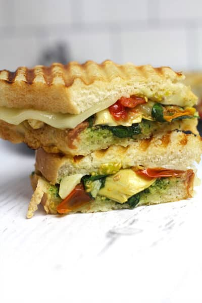 Side shot of a stack of two roasted vegetable pesto paninis, on a white background.