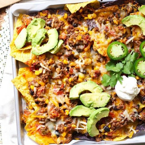 Overhead shot of a half of a sheet pan of beef and bean nachos, with toppings.