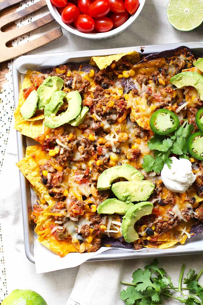 Beef and Bean Nachos are a perfect party food that everyone will love. Bake for just 15 minutes, top with your favorite condiments, and dig in! | suebeehomemaker.com