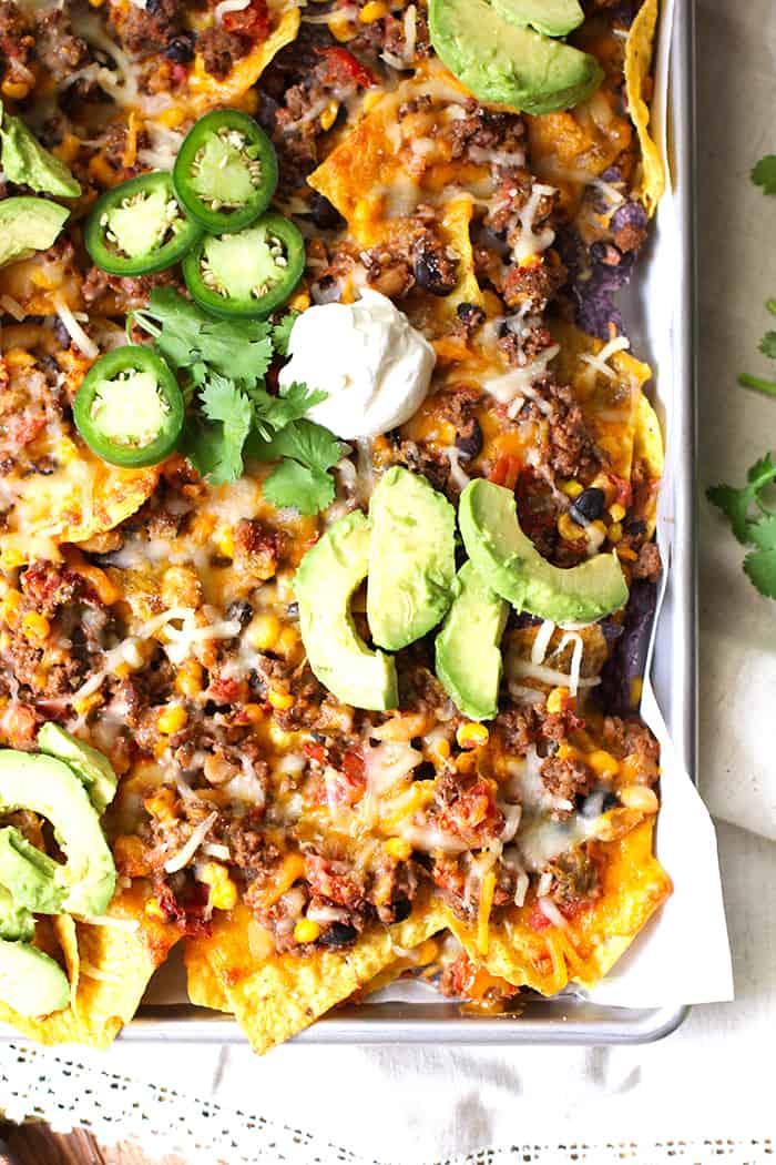 Close up shot of a corner of a sheet pan of beef and bean nachos.