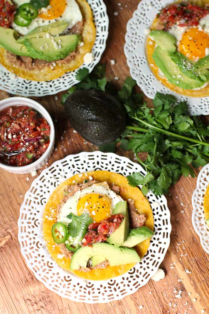Huevos Rancheros Tostadas is a classic Mexican dish, made with pinto beans, sunny side up eggs, cojita cheese, avocado slices, jalapeños, and a spoonful of salsa! | suebeehomemaker.com