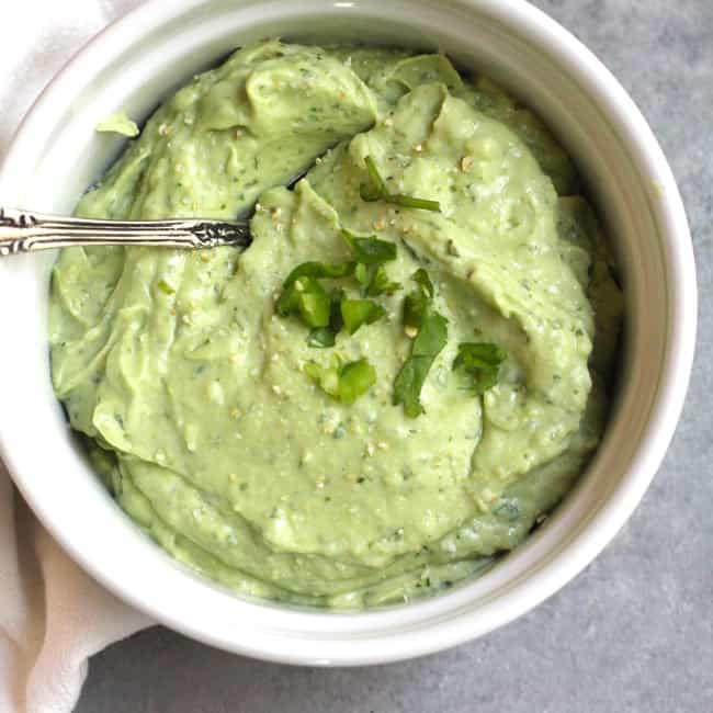 Overhead shot of a small white bowl with Avocado Crema, and a spoon inside.