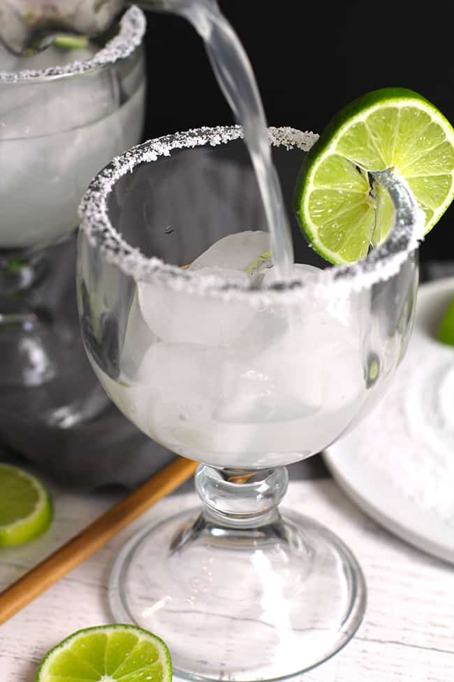 Side shot of a margarita glass, with skinny margarita being poured inside.
