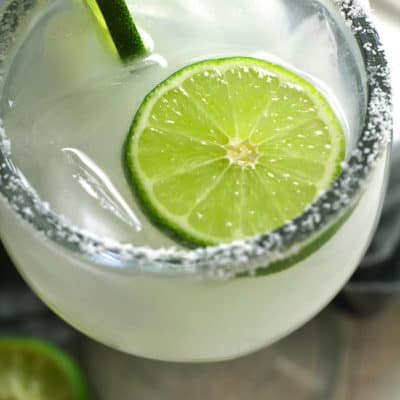 Overhead closeup shot of a classic skinny margarita, with a salt rim and some lime slices.