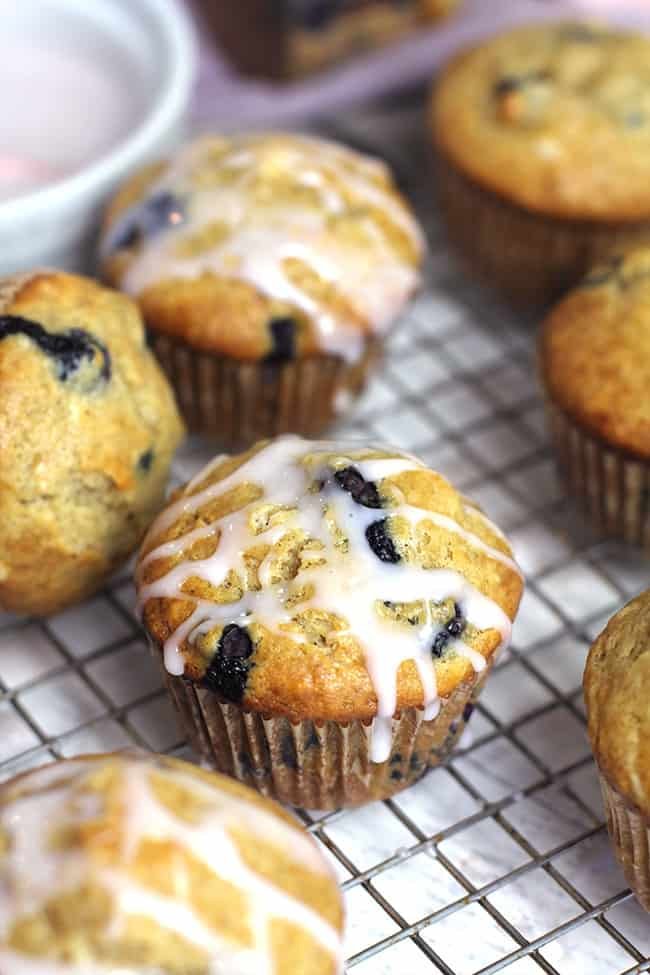 Side shot of the best blueberry muffins, with a glaze on the top, on a wire rack.