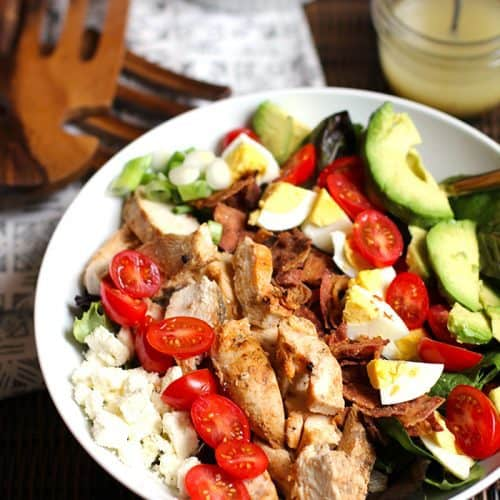 A salad bowl of chicken Cobb salad, with bacon, eggs, tomatoes, feta cheese, and avocado.