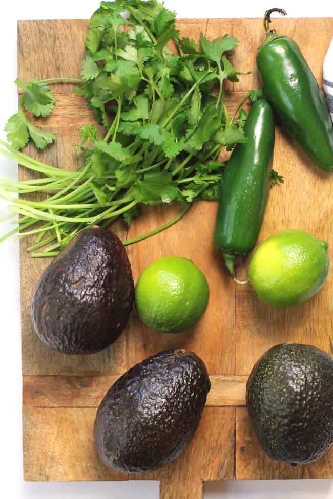 Overhead shot of the guacamole ingredients on a wooden board - avocados, limes, jalapeño, and cilantro.
