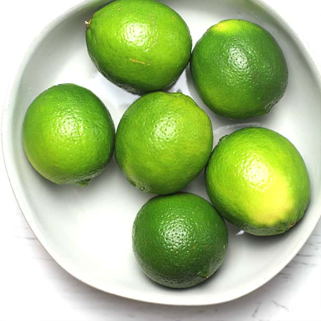 Overhead shot of a white bowl of six limes.