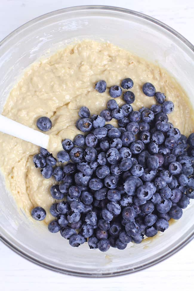 Overhead shot of a glass bowl of muffin batter with fresh blueberries on top.