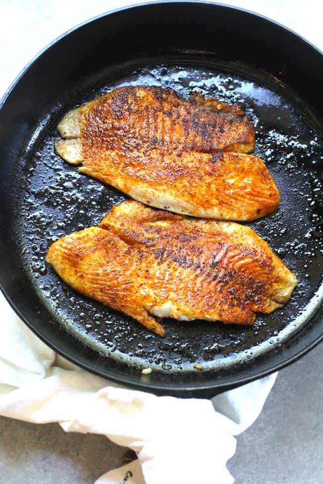 Overhead shot of two pieces of tilapia in a cast iron skillet.