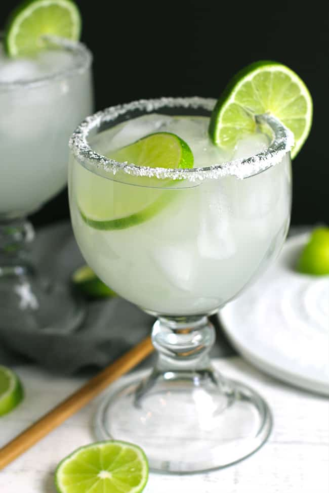 Side shot of two large classic skinny margaritas, with lime slices, against a black background.