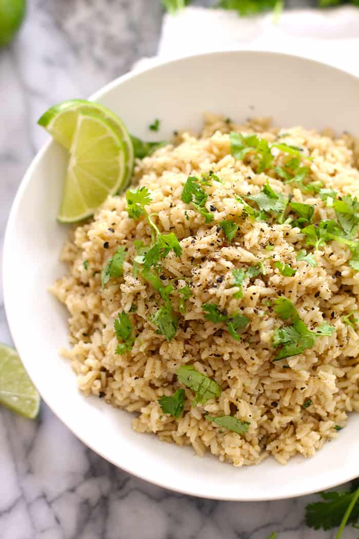 Cilantro Lime Rice makes a perfect Tex-Mex side, combining long grain brown rice with onions, garlic, cumin, cilantro, and freshly squeezed lime juice!   suebeehomemaker.com